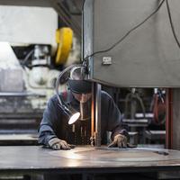 Caucasian worker using metal saw in workshop