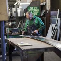 Caucasian worker using machinery in workshop