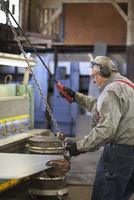 Caucasian worker hooking chain to sheet metal in workshop