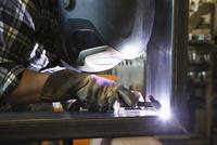 Black worker welding in workshop