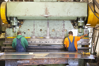 Caucasian workers using machinery in workshop