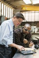 Worker and businessman using digital tablet in workshop 11018073444| 写真素材・ストックフォト・画像・イラスト素材|アマナイメージズ