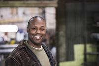 Black worker smiling in workshop 11018073463| 写真素材・ストックフォト・画像・イラスト素材|アマナイメージズ