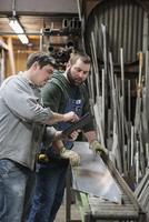 Caucasian workers examining sheet metal in workshop 11018073467| 写真素材・ストックフォト・画像・イラスト素材|アマナイメージズ