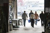 Workers exiting door of workshop