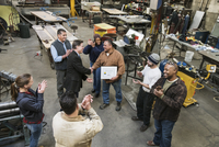 High angle view of worker and businessman shaking hands in workshop