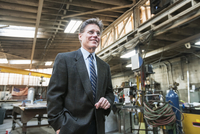 Caucasian businessman smiling in workshop