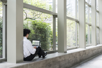 Hispanic businessman using laptop in office window