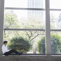 Hispanic businessman using laptop in window