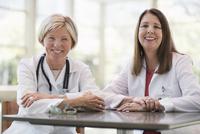 Caucasian doctors smiling in office