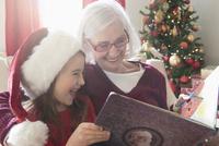 Caucasian grandmother and granddaughter reading Christmas book 11018073559| 写真素材・ストックフォト・画像・イラスト素材|アマナイメージズ