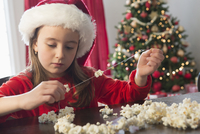 Caucasian girl stringing popcorn at Christmas