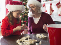 Caucasian grandmother and granddaughter stringing popcorn at Christmas