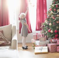 Caucasian girl cheering near Christmas tree 11018073566| 写真素材・ストックフォト・画像・イラスト素材|アマナイメージズ