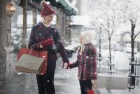 Caucasian grandmother and granddaughter shopping in snow 11018073575| 写真素材・ストックフォト・画像・イラスト素材|アマナイメージズ
