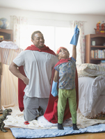 Father and son playing dress-up in bedroom