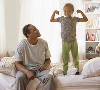 Boy flexing muscles for father in bedroom