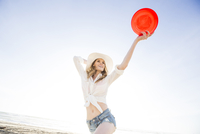 Caucasian woman holding plastic disc on beach