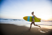 Caucasian woman carrying surfboard on beach