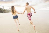 Caucasian couple running on beach