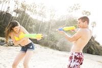 Caucasian couple playing with squirt guns on beach 11018073659| 写真素材・ストックフォト・画像・イラスト素材|アマナイメージズ