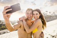 Caucasian couple taking selfie on beach 11018073663| 写真素材・ストックフォト・画像・イラスト素材|アマナイメージズ