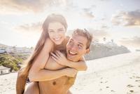 Caucasian man carrying girlfriend on beach