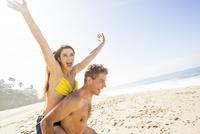 Caucasian man carrying girlfriend on beach 11018073668| 写真素材・ストックフォト・画像・イラスト素材|アマナイメージズ