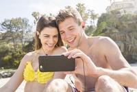 Caucasian couple using cell phone on beach 11018073669| 写真素材・ストックフォト・画像・イラスト素材|アマナイメージズ