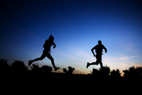Silhouette of Caucasian couple running at dawn
