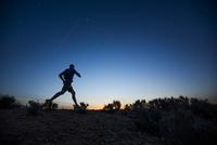 Silhouette of Caucasian teenage boy running at dawn