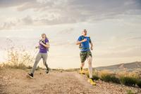 Caucasian couple running on remote hilltop 11018073673| 写真素材・ストックフォト・画像・イラスト素材|アマナイメージズ