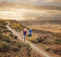 Caucasian couple running on remote dirt path 11018073676| 写真素材・ストックフォト・画像・イラスト素材|アマナイメージズ