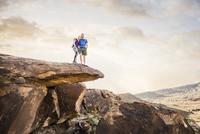 Caucasian couple on rock formation admiring landscape 11018073682| 写真素材・ストックフォト・画像・イラスト素材|アマナイメージズ
