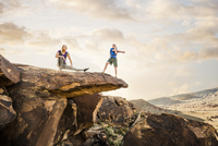 Caucasian couple stretching on rock formation