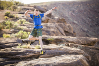 Caucasian teenage boy running on rock formation