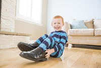 Caucasian boy wearing shoes of father in living room