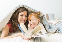 Caucasian mother and daughter reading book in bed