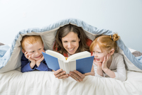 Caucasian mother and children reading book in bed