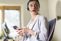 Businesswoman using cell phone and headset in office 11018073709| 写真素材・ストックフォト・画像・イラスト素材|アマナイメージズ