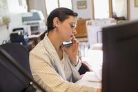 Businesswoman talking on cell phone in office 11018073715  写真素材・ストックフォト・画像・イラスト素材 アマナイメージズ
