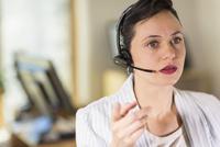 Businesswoman talking on headset in office