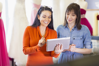 Hispanic entrepreneurs using digital tablet in bridal shop