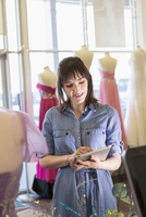 Hispanic entrepreneur using digital tablet in bridal shop
