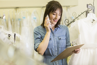 Hispanic entrepreneur talking on telephone in bridal shop