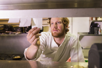 Caucasian chef reading orders in restaurant kitchen