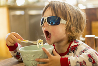Caucasian boy in sunglasses eating in kitchen