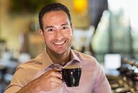 Hispanic barista drinking coffee in coffee shop