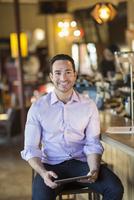 Hispanic businessman using digital tablet in coffee shop 11018073757| 写真素材・ストックフォト・画像・イラスト素材|アマナイメージズ