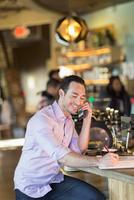 Hispanic businessman talking on cell phone in coffee shop 11018073760| 写真素材・ストックフォト・画像・イラスト素材|アマナイメージズ